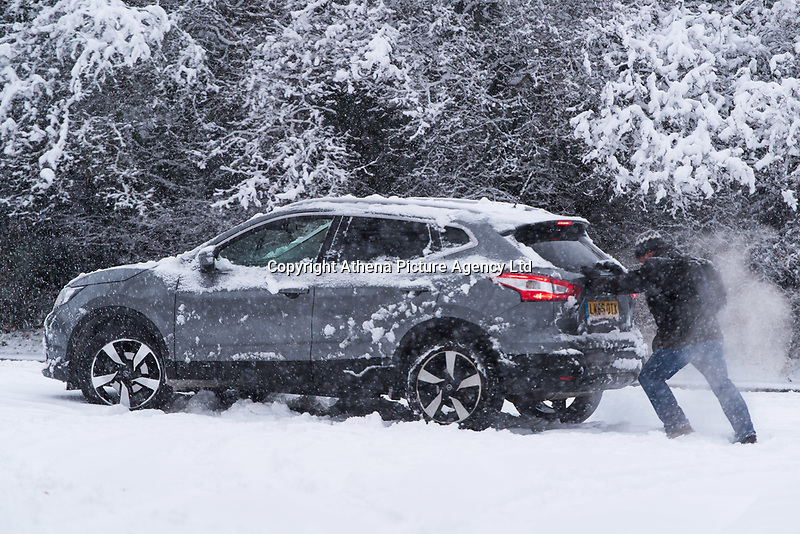 Passers by help push a 4x4 that got stuck in the snow in the village of Redbourn, Hertfordshire, UK. Sunday 10 December 2017.