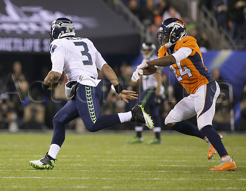 02.02.2014. East Rutherford, NJ, USA. Russell Wilson (3) of the Seattle Seahawks runs past Champ Bailey (24) of the Denver Broncos in the second half in Super Bowl XLVIII at MetLife Stadium in East Rutherford, N.J., on Sunday, Feb. 2, 2014
