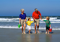 Grandparents and grandchildren playing at the beach.