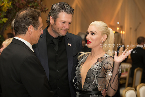 US entertainer Gwen Stefani (R), US entertainer Blake Shelton (C) and New York Governor Andrew Cuomo (L) attend a state dinner for Italian Prime Minister Matteo Renzi, hosted by US President Barack Obama, on the South Lawn of the White House in Washington DC, USA, 18 October 2016. President Obama hosts his final state dinner, featuring celebrity chef Mario Batali and singer Gwen Stefani performing after dinner. <br /> Credit: Michael Reynolds / Pool via CNP