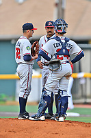 Danville Braves starting pitcher Dilmer Mejia (32), pitching coach Kanekoa Texeira (50) and catcher William Contreras (24) have a conversation on the mound during a game against the  Johnson City Cardinals at TVA Credit Union Ballpark on July 23, 2017 in Johnson City, Tennessee. The Cardinals defeated the Braves 8-5. (Tony Farlow/Four Seam Images)