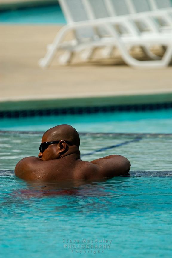 Black man wearing sunglasses resting in swimming pool at Playa Blanca Resort, Panama