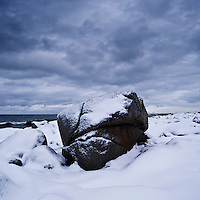 Snow covered boulder on coast, near Kvalness, Lofoten islands, Norway