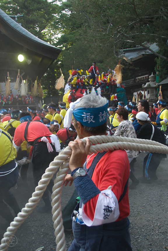 "An elderly man shoulders the ends of two thick ropes attached to the Fune Matsuri's (Boat Festival) ""boat"" - a large wooden sleigh-like float that is pulled through the streets and then three times around the shrine buildings each August 1. This festival is thought to reach back over a thousand years."