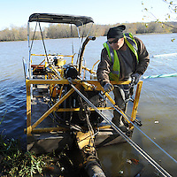 NWA Democrat-Gazette/ANDY SHUPE<br /> Selvin Calix of Kansas City, a worker with Stream, Lake &amp; Wetland Solutions in Linwood, Kan., prepares to start a dredge Thursday, Nov. 12, 2015, on the southeastern side of Lake Sequoyah as work begins to remove sediment and associated nutrients from the bottom of the lake to improve the lake and water quality. The company plans to remove 360 cubic yards of sediment per day with a goal of working 27 days before turning the longterm project over to city of Fayetteville contractors.