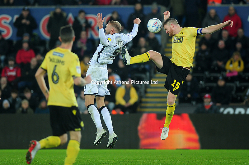Mike van der Hoorn of Swansea City is fouled by Alex Pearce of Millwall during the Sky Bet Championship match between Swansea City and Millwall at the Liberty Stadium in Swansea, Wales, UK. Saturday 23rd November 2019