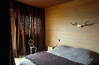 A lone pair of horns hangs above the bed in a simply decorated bedroom