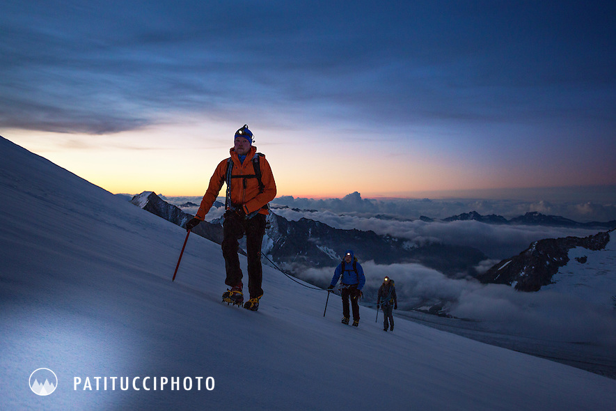 Climbers using headlamps at sunrise while climbing the Finsteraarhorn, Switzerland