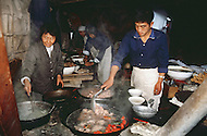 September, 1985. Shaanxi Province, China. Men and women cooking in a small restaurant in Wuqi area.
