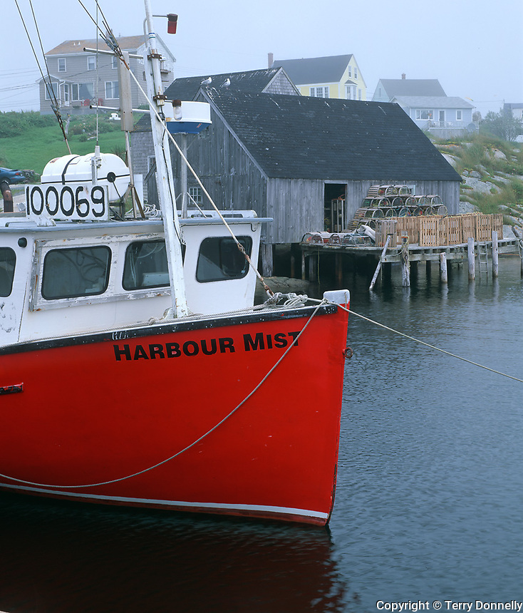 Halifax County, Nova Scota<br /> Fishing boat Harbor Mist with boat houses and homes of Peggy's Cove in fog