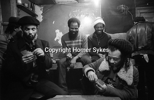 Frank Crichlow  in The Mangrove Restaurant, All Saints Road, Notting Hill Gate. West London 1978. From Left 2 Right: Speedy holding deck of cards, Frank Crichlow, Blues, Dutchy playing cards, Twist- with back to camera.