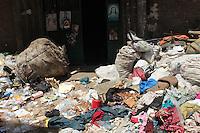 2011 Mokattam Garbage City (alla periferia del Cairo) il quartiere copto dove si vive in mezzo alla spazzatura raccolta: immondizia per terra davanti ad una porta a cui sono appesi dei manifesti religiosi con simboli cristiani.
