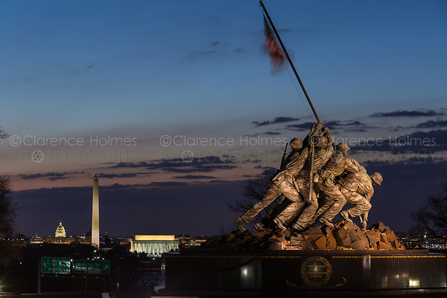 The US Marine Corps War Memorial with Washington landmarks in the background during morning twilight in Arlington, Virginia.