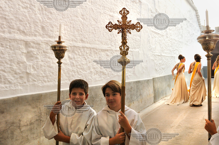 Altar boys carrying the processional cross and candles at the end of a  Catholic religious procession through the town of Campo de Criptana.