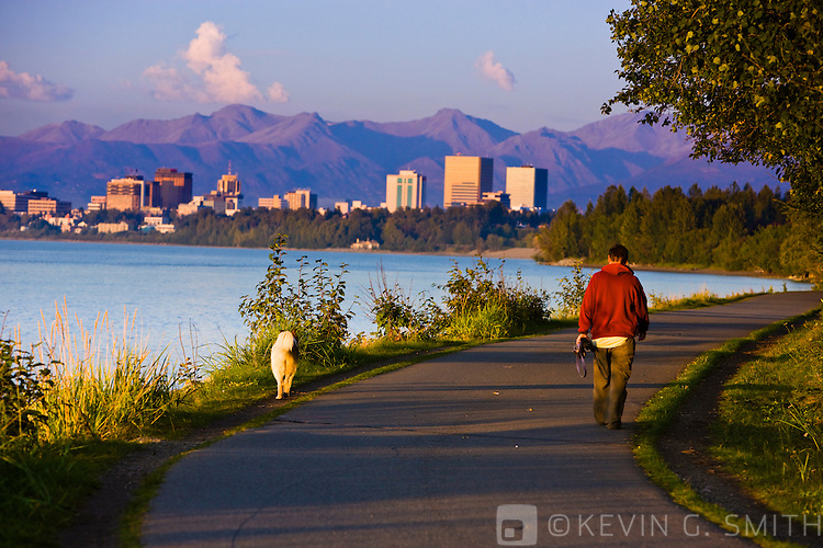 People using the Tony Knowles Coastal Trail,  Anchorage skyline in the distance, high tide, late summer, Anchorage, Southcentral Alaska, USA. Not Model Released