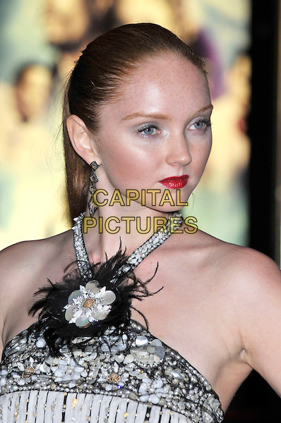"LILY COLE .Attending the UK film premiere of ""The Imaginarium Of Doctor Parnassus"" at the Empire Leicester Square cinema, London, England, UK, October 6th 2009..portrait headshot red lipstick ponytail hair up white beaded embellished jewel encrusted halterneck straps feathers feather flower corsage black earrings profile .CAP/PL.©Phil Loftus/Capital Pictures."