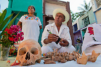 Doña Irma with Don Venancio Tuz Chi, bone cleaner, cleans his grandfathers bones at the Pomuch graveyard. Campeche, Mexico