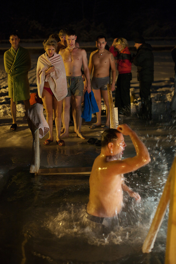Moscow, Russia, 18/01/2011..Bathers watch a man cross himself in the water as Orthodox Christian believers celebrate Epiphany at a lake in eastern Moscow. Priests blessed the waters and followers baptised themselves by total immersion in the freezing lake in temperatures of minus 15C.
