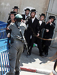 An ultra-Orthodox Jew is grabbed by an Israeli Border policeman during a protest in the coastal town of Jaffa, just south of Tel Aviv, on 12 August 2010 over the town's decision to remove ancient graves found during the construction of a hotel. Photo by Mahfouz Abu Turk