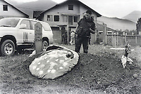 Fresh grave of a Kosovar Albanian guerilla near Pec/Peja. The body was exhumed from a mass grave after the war. In the background is a white sheet containing human remains that a family was coming to identify.