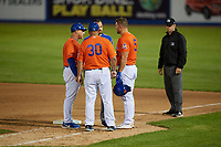 Syracuse Mets Tim Tebow (15) gets looked at by manager Tony DeFrancesco, coach Benny Distefano (30) and athletic trainer Grant Hufford after being hit in the head by a pitch during an International League game against the Charlotte Knights on June 11, 2019 at NBT Bank Stadium in Syracuse, New York.  First base umpire Brian Peterson looks on.  Syracuse defeated Charlotte 15-8.  (Mike Janes/Four Seam Images)