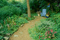 Blue chair and matching birdhouse circled by potted plants are the reward at the end of the garden path