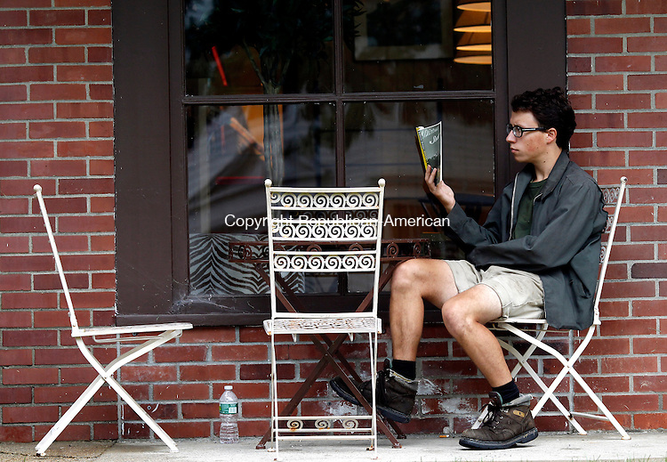 "Washington, CT- 15, August 2011-081511CM03  Ian Engelberger of Warren, enjoys ""Distance Start, a book written by Roberto Bolano, outside of Marty's Cafe in Washington Monday afternoon. According to the National Weather Service the rain is expected to continue today with a chance of showers, mainly before 5pm. Otherwise it's expected to be cloudy, with a high near 72.  Christopher Massa Republican-American"