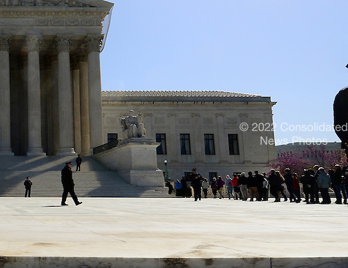 Spectators who want to witness the proceedings line up outside the United States Supreme Court Building as oral arguments concerning the Constitutionality of the U.S. Health Care Law continue inside the Court.  .Credit: Ron Sachs / CNP