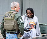 WATERBURY,  CT-051719JS07- A DEA officer talks with a resident who was detained during a search of a home on Bank Street during a city-wide operation on Friday as Waterbury police along with cooperation from State Police, Watertown Police, the States Attorney's Office, the DEA and ATF, conducted search and seizures as well as searching for wanted suspects who police say were suspected in the sale of heroin.<br /> Jim Shannon Republican American