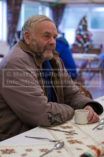 At a Christmas shelter for the vulnerable and homeless, a man waits for Christmas dinner to be served.