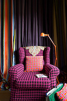 An old-fashioned wing-backed armchair in the study has been covered in a checked Chanel-style tweed with an embroidered 19th century Indian lace fichu on the backrest