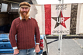 USA, Oregon, Ashland, Upper Rogue Organics farmer Ryan Navickas by his truck at the Rogue Valley Growers and Crafters Market