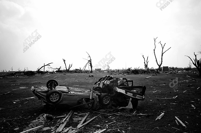 The force of the storm crushed these two vehicles together which landed in middle of field. Joplin, Mo. May 25, 2011...