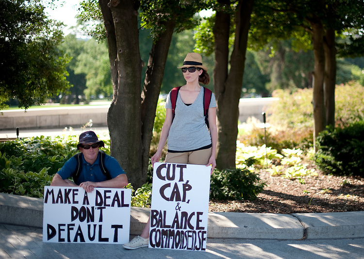 UNITED STATES - JULY 30: John and Sarah Moore, of Stafford, Va., try to keep cool in the shade at the Capitol as they express their views on the debt ceiling crisis on Saturday afternoon, July 30, 2011. The couple said that while they tend to side more with the Republican approach, they want Congress to make a deal so the U.S. doesn't default on its debts. (Photo By Bill Clark/Roll Call)