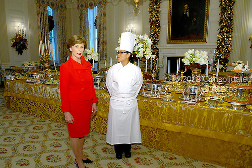 Washington, DC - November 29, 2007 -- First lady Laura Bush, left and White House Executive Chef Cristeta Comerford, right show the holiday buffet during the preview the 2007 White House Christmas Decorations on the State Floor of the White House in Washington, D.C. on Thursday, November 29, 2007..Credit: Ron Sachs / CNP