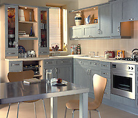 A modern kitchen with grey painted units and a wooden floor. A stainless steel table and wooden chairs are placed in the centre of the room.