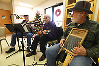NWA Democrat-Gazette/FLIP PUTTHOFF <br /> WASH-DAY PERCUSSION<br /> Jeff Davis plays a washboard on Tuesday Dec. 4 2018 with the Old Town String Band at the Billy V. Hall Senior Activity and Wellness Center in Gravette. Al Blair (left) and Henry Easter follow Davis's rhythm. The band features musicians on guitar, mandolin, fiddle, ukelele, bass and more. They play at the Gravette senior center at 10 a.m. the first, second and third Tuesday of each month
