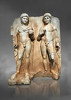Roman Sebasteion relief  sculpture of  Two princes, Aphrodisias Museum, Aphrodisias, Turkey. Against a grey background.<br /> <br /> Two princes stand like statues, naked, wearing cloaks. The left figure holds the orb of the world in one hand, a symbol of  world rule that indicates he is the imperial heir, and in the other a ship&rsquo;s stern ornament (aphlaston), a symbol of naval victory. They and probably Gius and Lucius, the grandsons of Augustus, or Nero and Britanicus, Claudius&rsquo; heir.