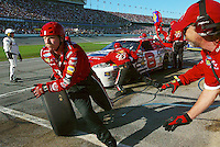 Danny Eranhardt, Dale Earnhardt Jr.'s uncle, left, chases a tire which got loose during a pit stop during the Daytona 500 at the Daytona International Speedway in Daytona Beach Sunday February 15, 2004. Earnhardt went on to win the race.(Kelly Jordan)