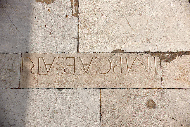 Roman lettering in the reused masonary from an earlier Roman temple in the exterior of the Duomo Pisa, Italy. This stone was placed upside.