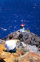A hiker stops to take in the beauty of the Makapuu Lighthouse located on Makapuu Point, eastern shore of oahu.