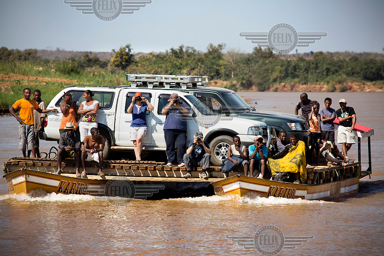 Tourists snap away with their cameras as they cross the Tsiribihina River with their 4 x 4 vehicles on a raft.