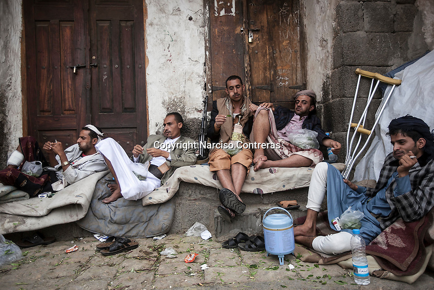 Monday 20 July, 2015: Residents and supporters of the Houthi insurgency are seen chewing Khat at the dusk in one street in the Old City of Sana'a, a 2,500-year-old cultural heritage site endangered after a fighter jet of the Saudi-led coalition bombed and destroyed a line of residential tower-houses killing 4 residents and reducing to rubble the historial site. The ongoing aerial campaign of bombardments by the Arab states and their western allies led by Saudi Arabia and the heavy fighting against the entrenchment of the Houthi insurgency along the Yemeni main cities from north to south has caused an international alert for the enlisted cultural heritage sites in Yemen, such as the historic town of Zabid, the Old City of Sana'a and the Old Walled City of Shibam. (Photo/Narciso Contreras)