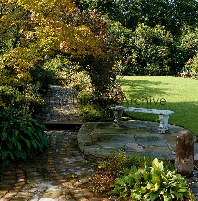 A cobbled path leads under a maple (Acer) arch with a stone bench overlooking the lawn