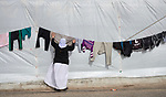 Adlane Saido hangs laundry to dry in a camp for internally displaced Yazidis at Dawodiya in Iraq's Kurdistan region. More than 600 Yazidi families living in the camp escaped from their communities in the Sinjar region during the attempted genocide by the Islamic State group. Although ISIS was militarily defeated in 2017, camp residents say it's still not safe for them to return home, nor do they have sufficient resources to rebuild their homes.<br /> <br /> The Lutheran World Federation, a member of the ACT Alliance, provides water, sanitation, garbage collection, and psycho-social support for the families in the camp.