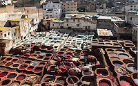 General view of Chouara tannery, Fez, Morocco, pictured on February 21, 2009 at midday. The Chouara tannery is the largest of the four ancient tanneries in the Medina of Fez where the traditional work of the tanners has remained unchanged since the 14th century. It is composed of numerous dried-earth pits where raw skins are treated, pounded, scraped and dyed. Tanners work in vats filled with various coloured liquid dyes derived from plant sources. Colours change every two weeks, poppy flower for red, mint for green, indigo for blue, chedar tree for brown and saffron for yellow. Fez, Morocco's second largest city, and one of the four imperial cities, was founded in 789 by Idris I on the banks of the River Fez. The oldest university in the world is here and the city is still the Moroccan cultural and spiritual centre. Fez has three sectors: the oldest part, the walled city of Fes-el-Bali, houses Morocco's largest medina and is a UNESCO World Heritage Site;  Fes-el-Jedid was founded in 1244 as a new capital by the Merenid dynasty, and contains the Mellah, or Jewish quarter; Ville Nouvelle was built by the French who took over most of Morocco in 1912 and transferred the capital to Rabat. Picture by Manuel Cohen.
