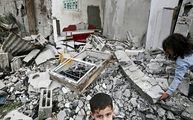 A Palestinian children in the rubble of a destroyed building following an Israeli air strike in the east of Jabaliya refugee camp on, 12 March 2012. Reports state that an Israeli air strike on the northern Gaza Strip's Jabalia refugee camp, on 12 March 2012, killed a 65-year-old man and his 30-year-old daughter, Palestinian medical officials and witnesses said. Their deaths bring to five the number of Palestinians killed Monday, and to 23 since the latest Israeli-Palestinian escalation began on Friday. Photo by Ali Jadallah