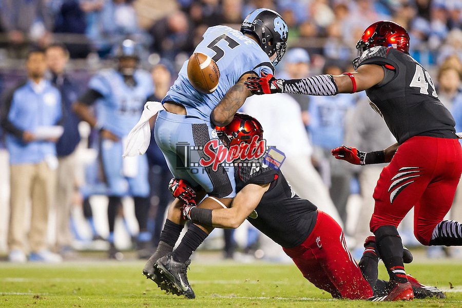 T.J. Thorpe (5) of the North Carolina Tar Heels fumbles the ball as he is hit by Tshumbi Johnson (20) of the Cincinnati Bearcats in the Belk Bowl at Bank of America Stadium on December 28, 2013 in Charlotte, North Carolina.  The Tar Heels defeated the Bearcats 39-17.   (Brian Westerholt/Sports On Film)