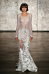 Model walks runway in a dimensional lace deep v gown with appliquéd skirt and attached lariat beaded necklace and long crochet lace sleeves, from Inbal Dror Fall 2018 bridal collection on October 5, 2017; during New York Bridal Fashion Week.