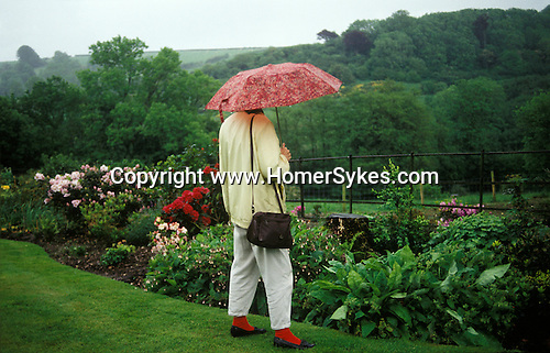Woman stands under her umbrella in heavy rain while visiting Broad Oak village garden open day Somerset